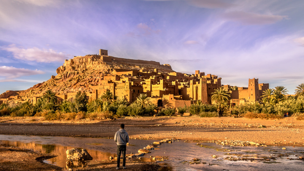 Liam gazing at Moroccos Ait Ben Haddou at sunset. Purple sky with a golden Kasbah