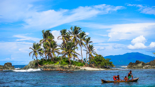Small san blas island with 3 local kids diving from a canoe