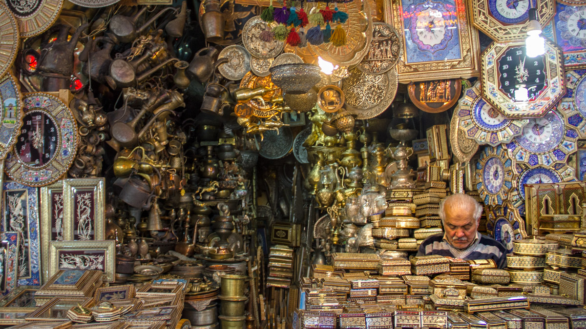 Shop keeper selling golden boxes in the bazaars of Iran